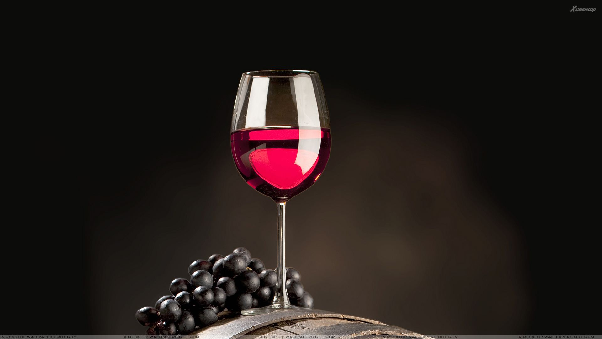 Red Wine With Black Grapes On Wooden Drum